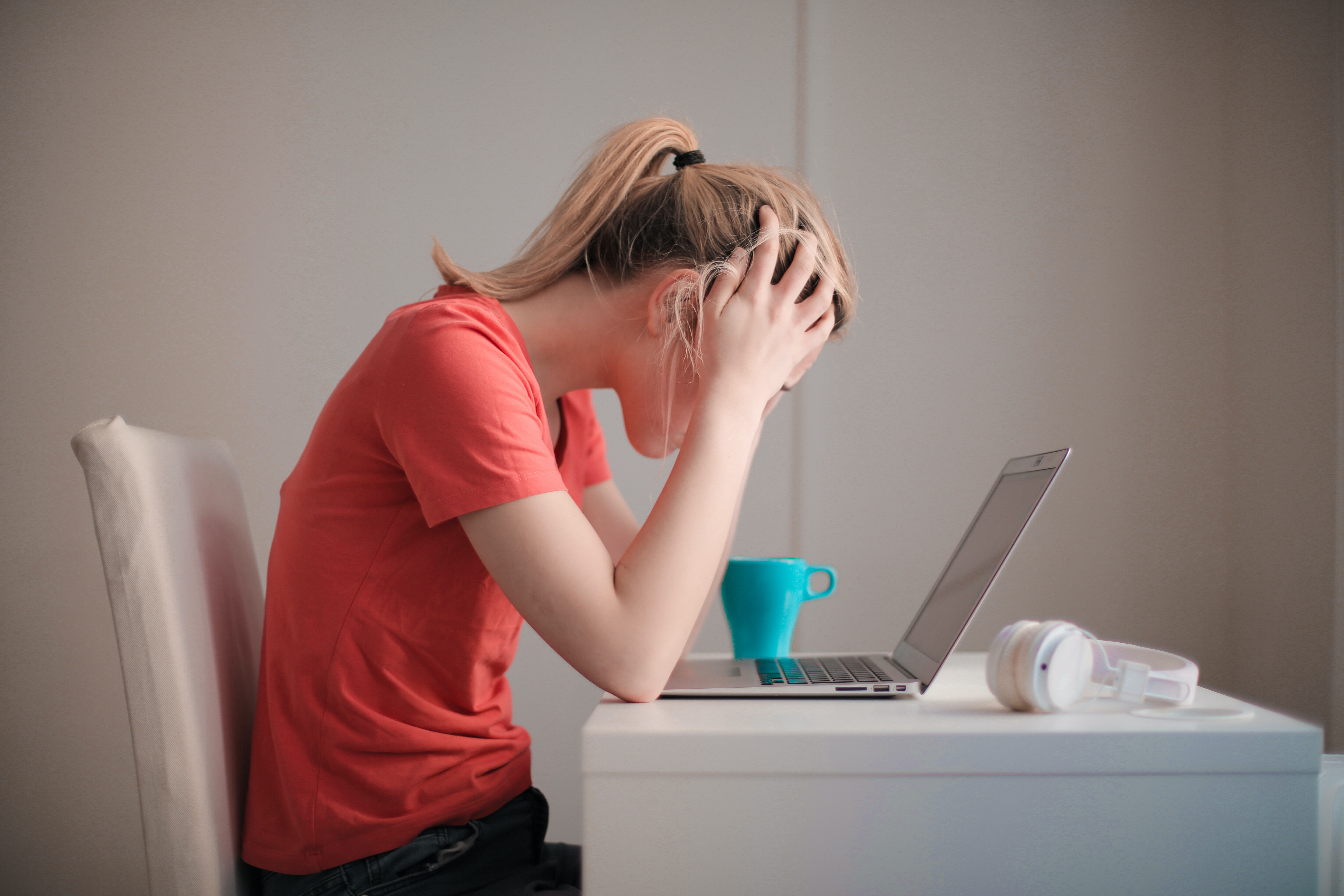 Woman in red t-shirt looking at her laptop, stressed.